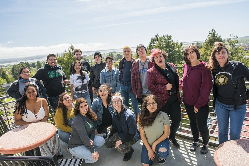 Group of students stand on the BSS balcony smiling